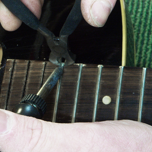 removing old frets with plier and soldering iron