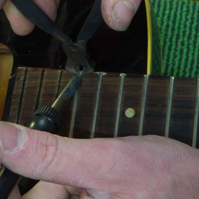 de oude fretten verwijderen met een tang en soldeerbout
